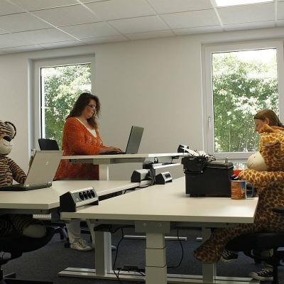 SChreibtische, zwei Personen stehen am Schreibtisch, zwei große Kuscheltiere sind als arbeitende drapiert